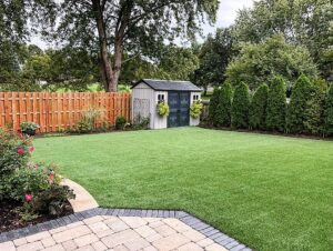 A Chicago backyard is shown with artificial turf, a patio, planted bushes and trees, and garden shed.